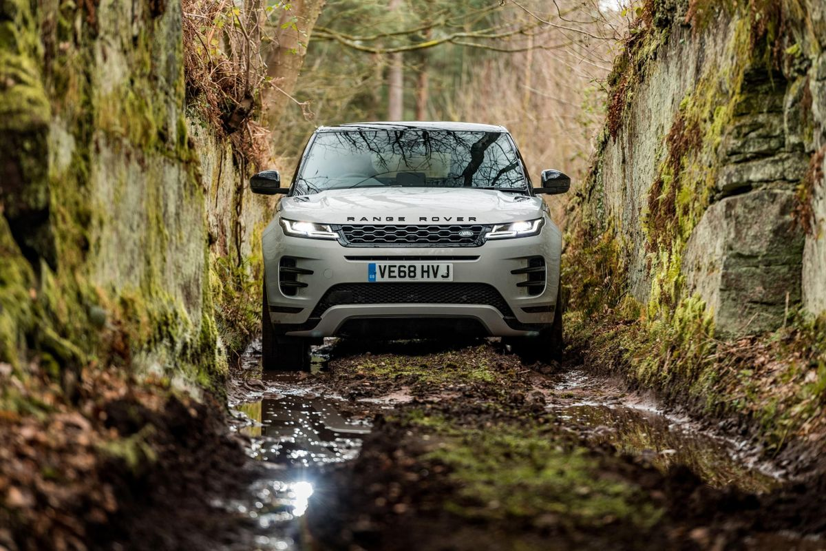 Silver Range Rover Evoque SUV drives through muddy tunnel