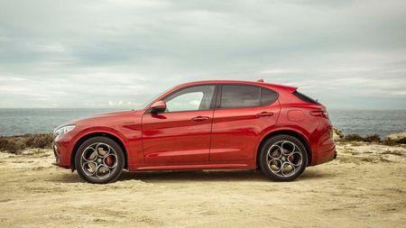 Red Alfa Romeo Stelvio parked on a coastal headland