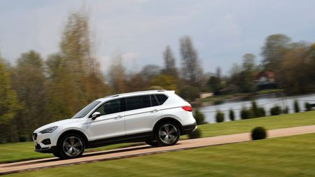Side view of a white Seat Tarraco driving through a park