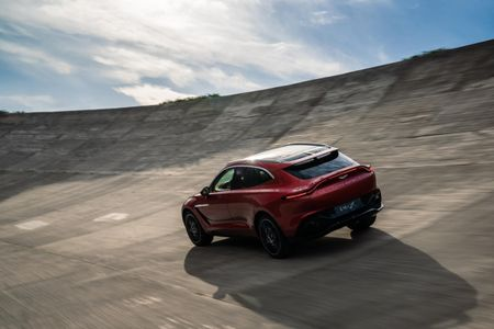 Red Aston Martin DBX driving away from the camera, against a blue sky and smooth concrete road