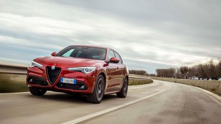 Red Alfa Romeo Stelvio driving on an open road