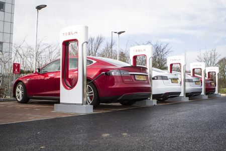 Red Tesla at a dedicated charging station