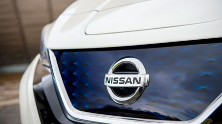 Close up of a white Nissan Leaf's badge