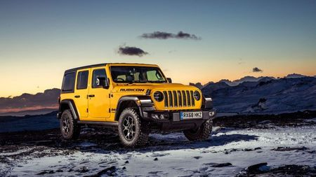 Yellow Jeep Wrangler parked on snowy ground, backed by an early sunrise