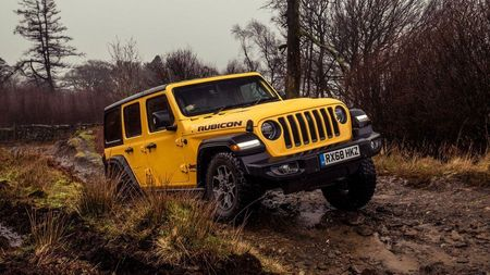 Yellow Jeep Wrangler offroading through mud