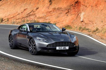 Black Aston Martin DB11 driving past orange cliffs