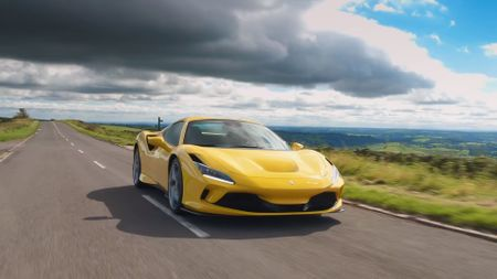 Yellow Ferrari F8 Spider drives down road with heavy cloud behind