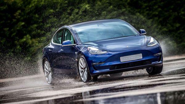 Blue Tesla Model 3 saloon driving through rain