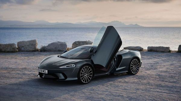 Black McLaren GT Coupe parked near a waterfront