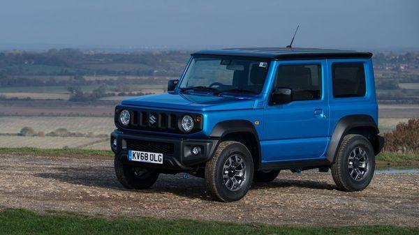 Blue Suzuki Jimny parked on dry grass