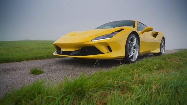Yellow Ferrari F8 Spider parked near green grass