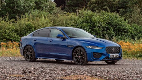 Blue Jaguar XE Saloon parked in front of yellow flowers
