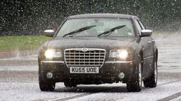 a saloon car driving in snow and winter