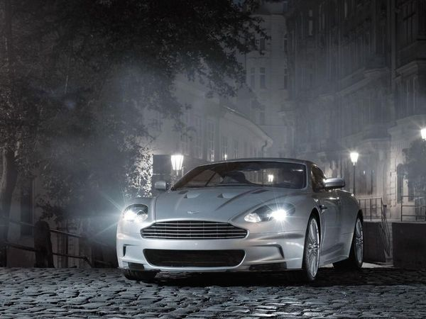 A silver Aston Martin DBS at night time