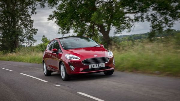 Red Ford Fiesta driving on a country road