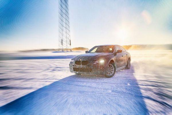 BMW i4 electric car drives through snow