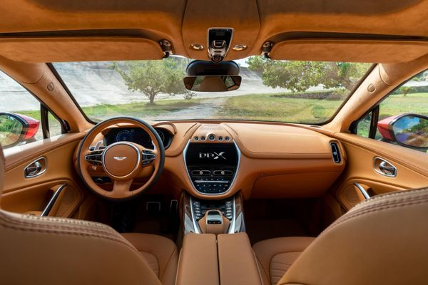 The Aston Martin DBX's tan leather interior, including steering wheel and a view of the forest through the windscreen
