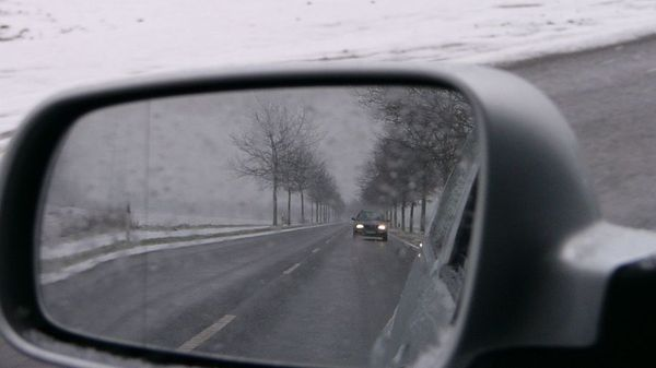 A car seen in a wing mirror, driving on a snowy day