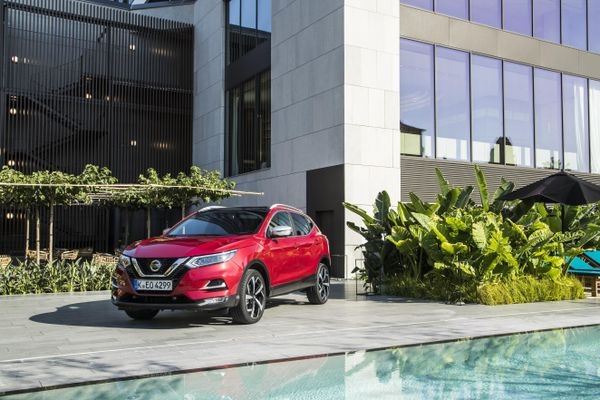 Red Nissan Qashqai lease car parked outside a modern house with swimming pool
