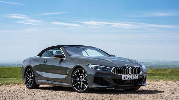 BMW 8 Series convertible parked in front of a blue sky