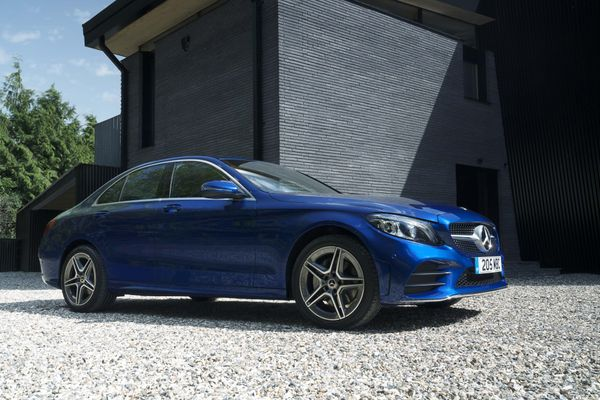 Blue Mercedes C Class lease car parked outside a grey house