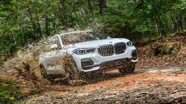 White BMW X5 offroading through a forest and splashing mud