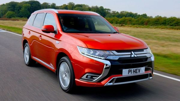 Red Mitsubishi Outlander Hybrid driving on a country lane