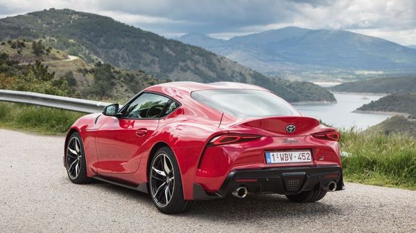 Red Toyota Supra coupe parked in a mountain range