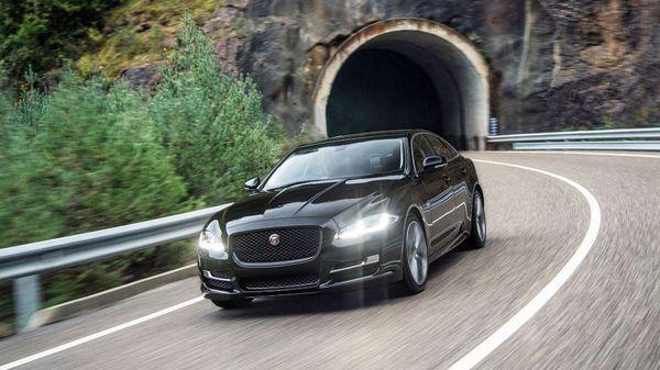 Black Jaguar XJ drives out of dark tunnel