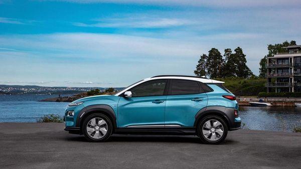 Blue Hyundai Kona parked against a blue sky