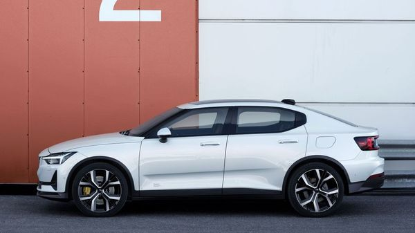 White Polestar 2 (2020 edition) parked against a storage unit