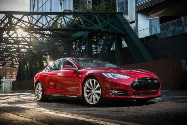 Red Tesla Model S in an industrial complex