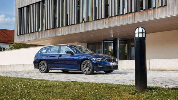 Blue BMW 3 Series Touring parked in front of a modern home