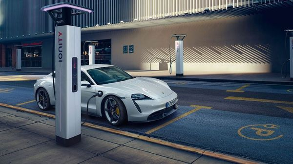 White Porsche Taycan charging in a blue public charging spot
