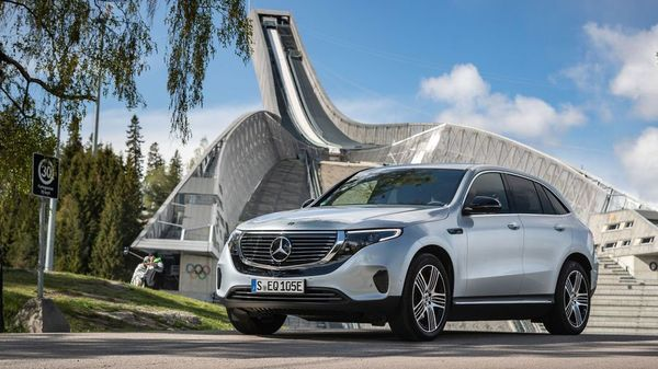 Silver Mercedes-Benz EQC parked in front of a modern building