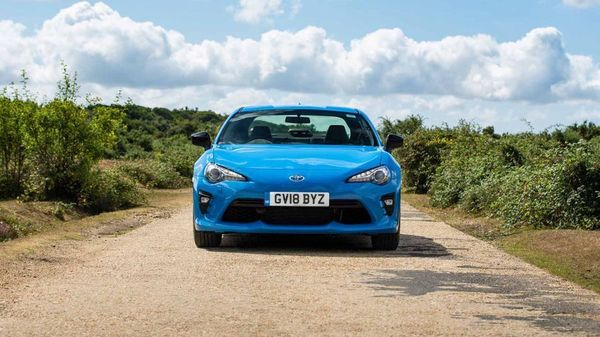 Blue Toyota GT86 on a dusty track