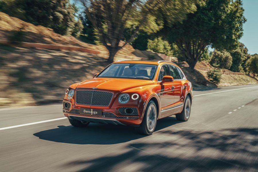 Orange Bentley Bentayga Hybrid driving through trees
