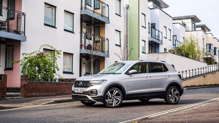 White Volkswagen T-Cross parked in front of colourful apartments