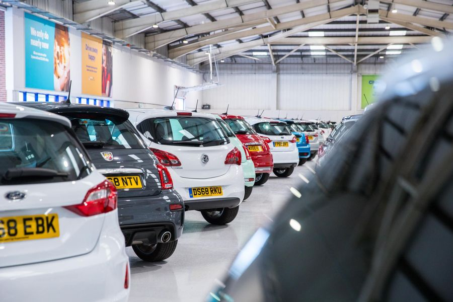 A car showroom with multiple cars parked inside