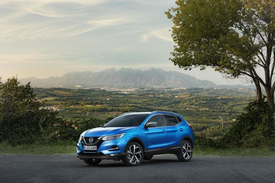 Blue Nissan Qashqai parked by tree in mountainous area