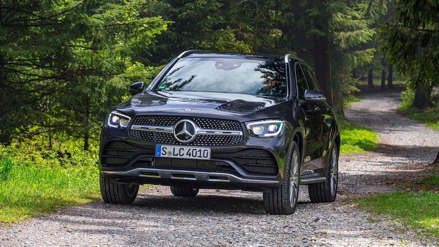 Black Mercedes-Benz GLC driving through a woodland