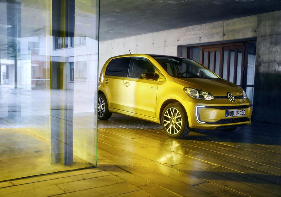 Yellow VW E Up electric car parked in a gold-lit garage