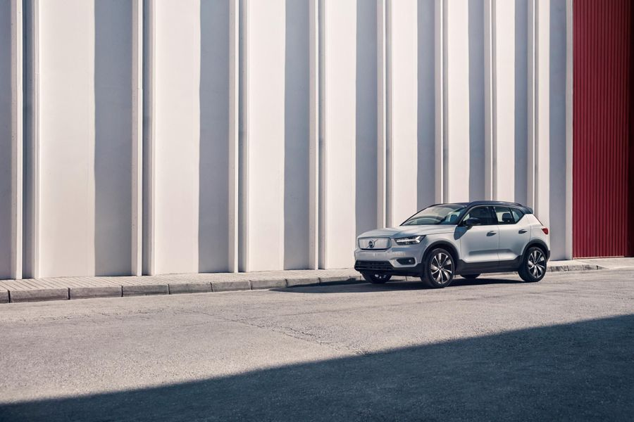 White Volvo XC40 parked in front of a white and red building