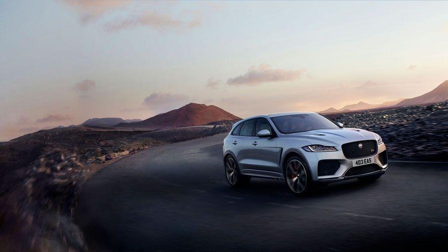 Jaguar F-Pace driving on a hill top against a gentle sunrise