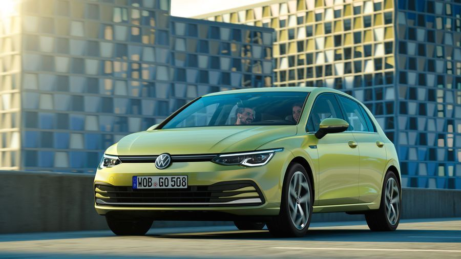 Green Volkswagen Golf parked in front of modern office blocks