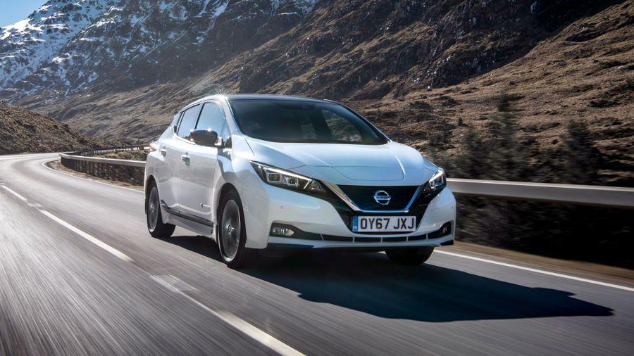 White Nissan Leaf driving through mountain range