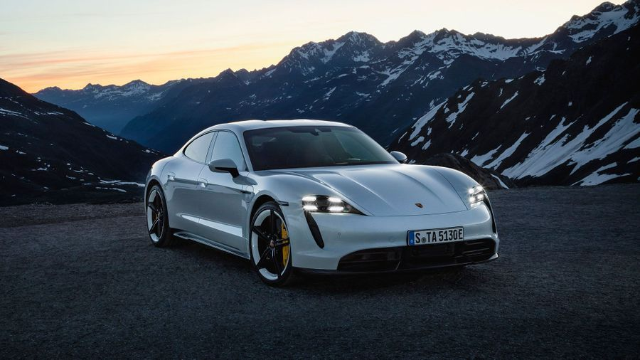 White Porsche Taycan parked in front of a snowy mountain
