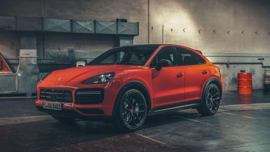 Bright orange Porsche Cayenne Coupe parked in a garage