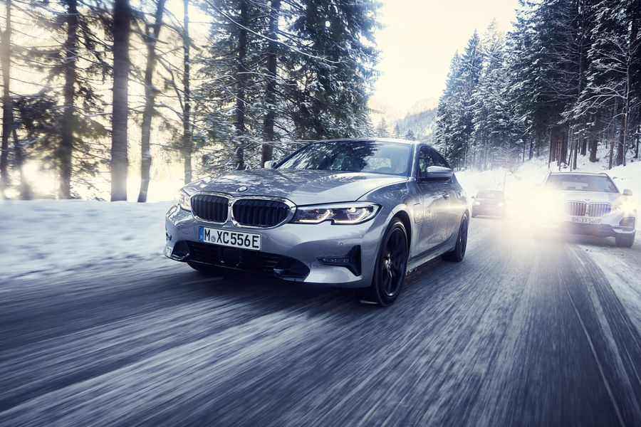 Silver BMW 330e driving through a snowy forest