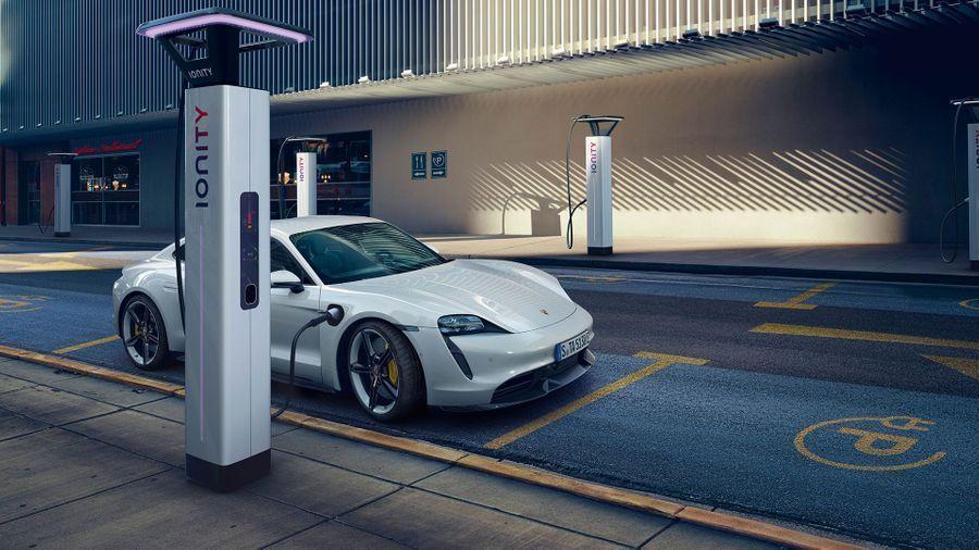 White Porsche Taycan electric car charging in public